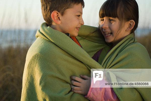 Kinder zusammen in Decke gewickelt im Freien  Portrait