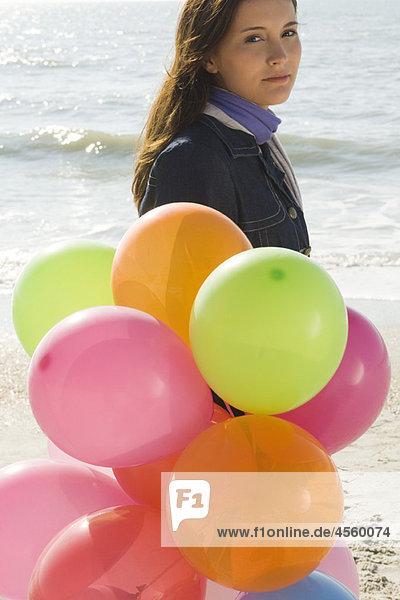 Preteen Mädchen mit einem Haufen Luftballons  die am Strand laufen.