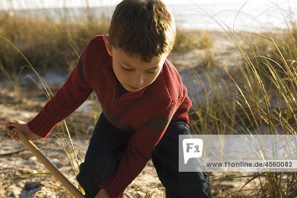 Junge beim Graben mit Schaufel auf Grasdüne  Strand und Meer im Hintergrund