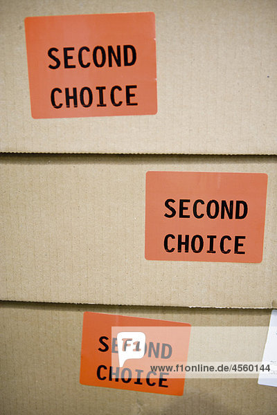 'Cardboard boxes labeled with stickers reading ''second choice'''