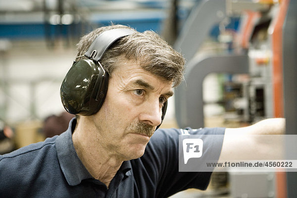 Factory worker wearing protective headphones