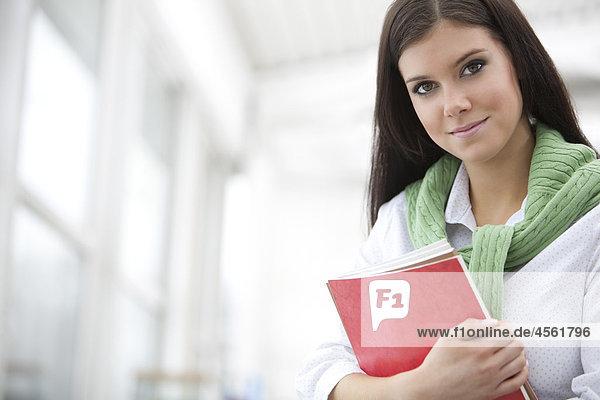 Portrait of junge Frau hält Bücher