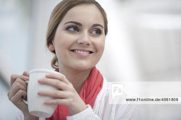Portrait of junge Frau hält Kaffeetasse