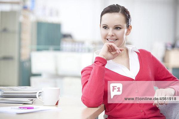 Porträt der jungen geschäftsfrau an Schreibtisch sitzen