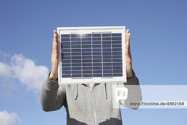 detail of woman holding solar panel up against sky