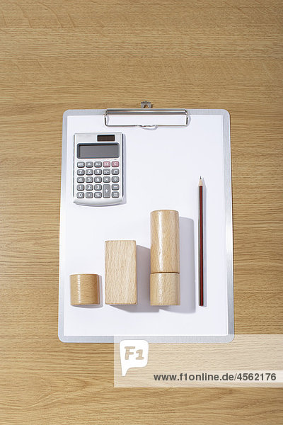 still life of clipboard calculator and wooden pieces