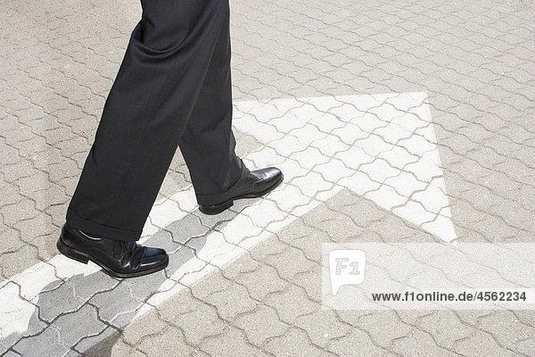 Detail des Business Person zu Fuß auf Pflaster mit Pfeil