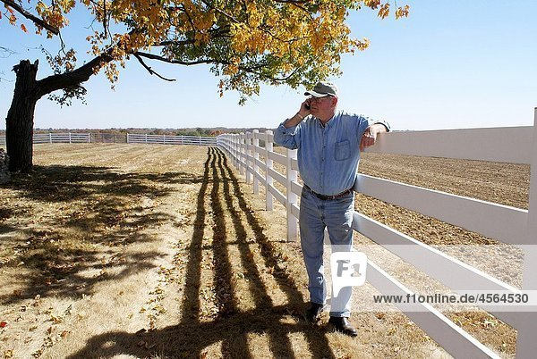 Senior man talks on cell phone by fence and harvested field