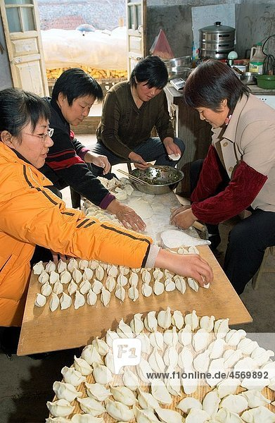Women making preparing traditional dim sum Chinese dumplings in farmhouse kitchen  Shandong Province  China
