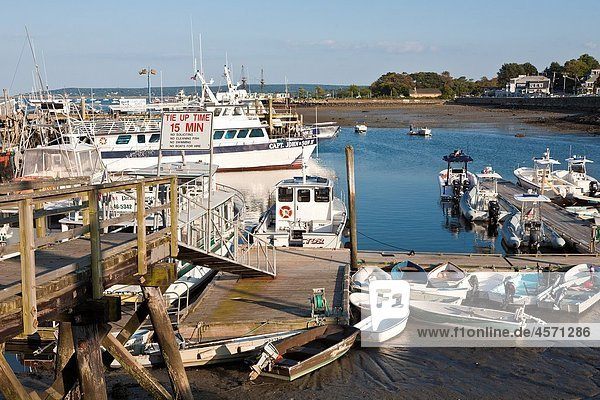 Small boats tied to floating dock in Plymouth Harbor in Plymouth Massachusetts