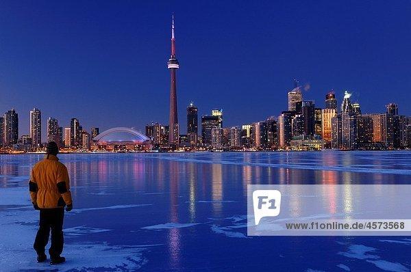 Man standing on frozen Lake Ontario watching Toronto city skyline light up at dusk