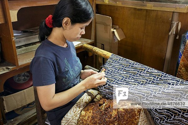 Indonesian woman making batik with with hot wax at a batik factory in Yokyakarta  Central Java  Indonesia