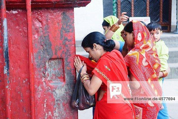 Hindu pilgrims praying at a shrine in Durbar Square in Kathmandu  Nepal