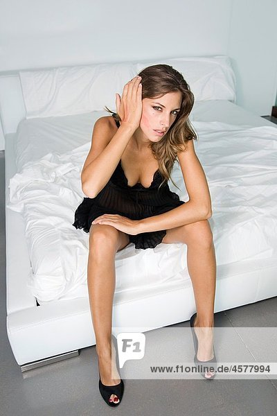 Woman sitting on bed  wearing high heels and lingerie