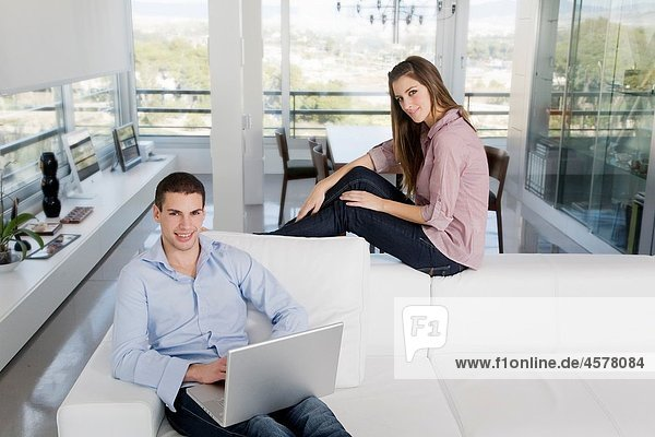 Portrait of a young couple sitting on the sofa using laptop