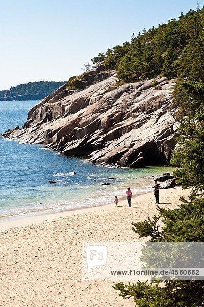 Visitors play at Sand Beach in Acadia National Park near Bar Harbor  Maine