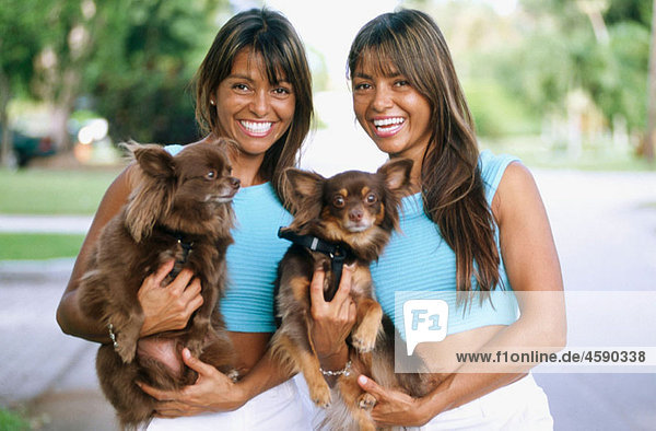 identical twins with indentical Yorkie dogs