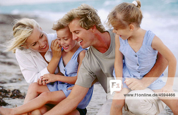Mom & dad with twin girls at the beach
