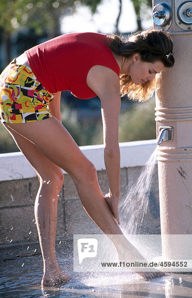 woman washing her legs in an outdoor shower