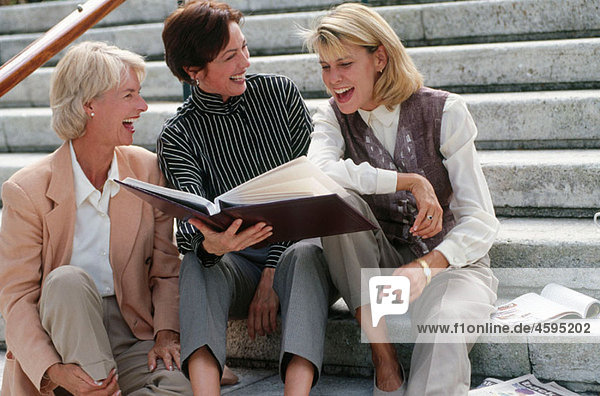women looking at a picture album
