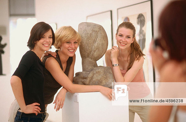 girl photographs her girlfriends at an art gallery