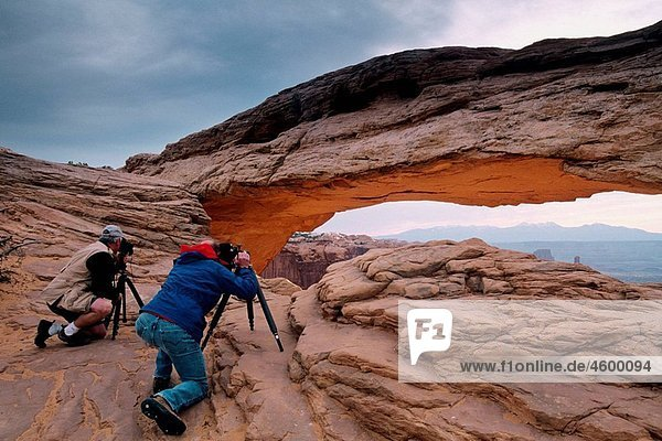 Photographer taking pictures of Mesa Arch  Island in the Sky District  Canyonlands National Park  Utah  USA