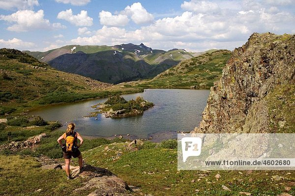 Female hiker pauses to take in the view above Highland Mary Lakes in the Weminuche Wilderness  San Juan Mountains  Colorado  USA