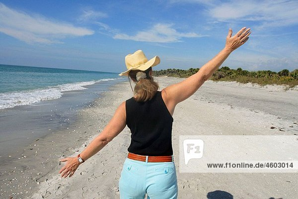 Senior woman walking at Casperson Beach in Venice (Florida  USA) with arms wide open