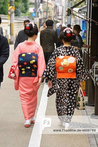 Two maiko  apprentice geisha wearing kimono  walking down a street in the Gion district of Kyoto