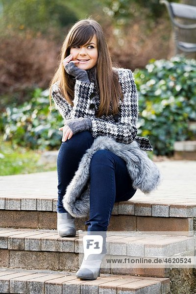 Fashionable young woman is sitting on a staircase in the park