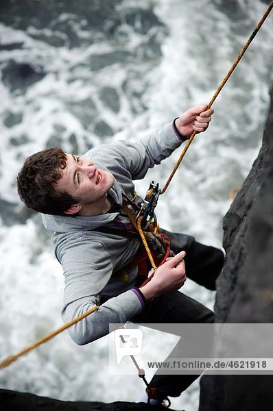 Learning the ropes: Aberystwyth university students abseiling on the sea wall  training for climbing   Wales UK