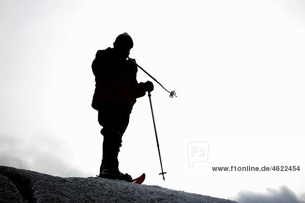 Appalachian Trail - The silhouette of a hiker on the summit of Mount Garfield during the winter months Located in the White Mountains  New Hampshire USA Model Release Yes Reference number 104