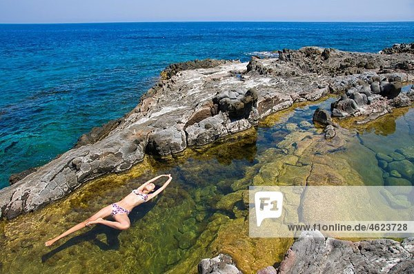 Woman floating in colorful water pool by the sea Pantelleria Island  Sicily  Italy