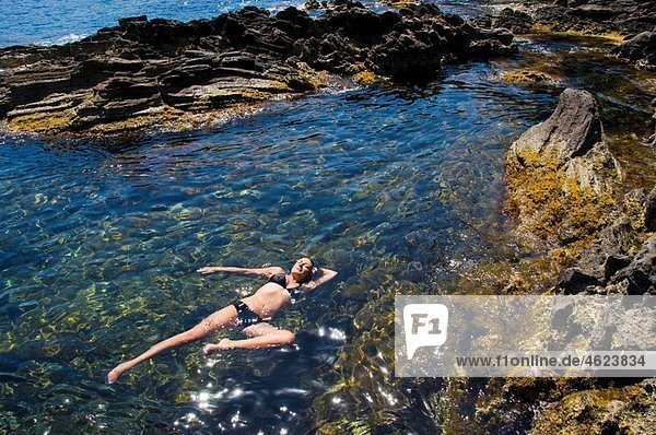 Woman floating in the Mediterranean water Island of Pantelleria  Sicily  Italy