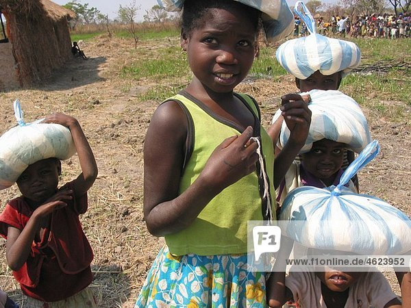 Young children carry bags of food on their heads after leaving an MSF feeding clinic Feeding centres and other humanitarian aid were organised in Angola after widescale malnutrition during and following the country¥s civil war