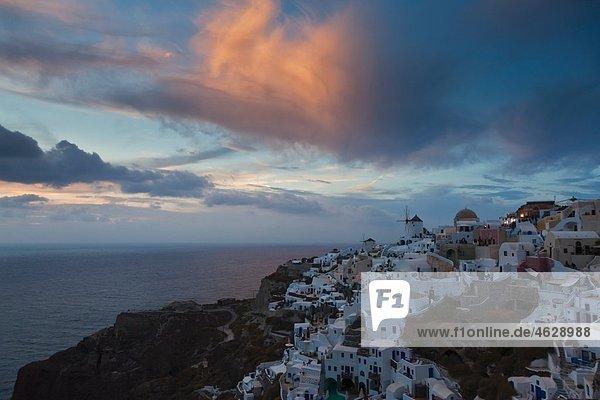 Griechenland  Kykladen  Thira  Santorini  Blick auf Oia und Windmühlen bei Sonnenuntergang