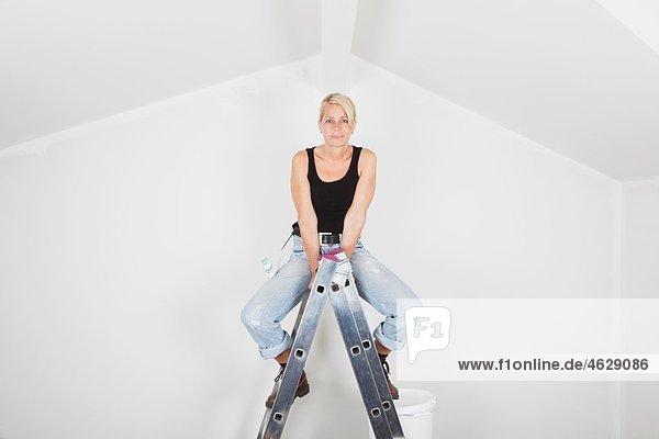 Reife Frau fertig auf Leiter mit Farbeimer und Roller zum Bemalen des Satteldaches