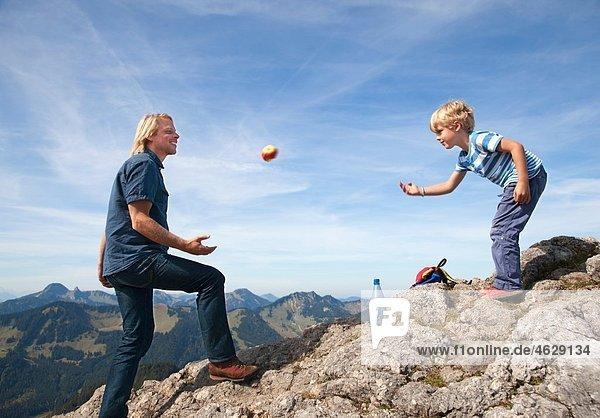 Deutschland  Bayern  Vater und Sohn (4-5 Jahre) spielen auf dem Berggipfel