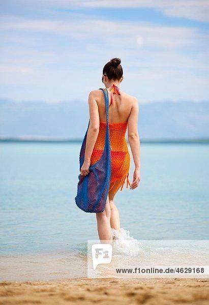 Kroatien  Zadar  Junge Frau beim Spaziergang im Wasser am Strand