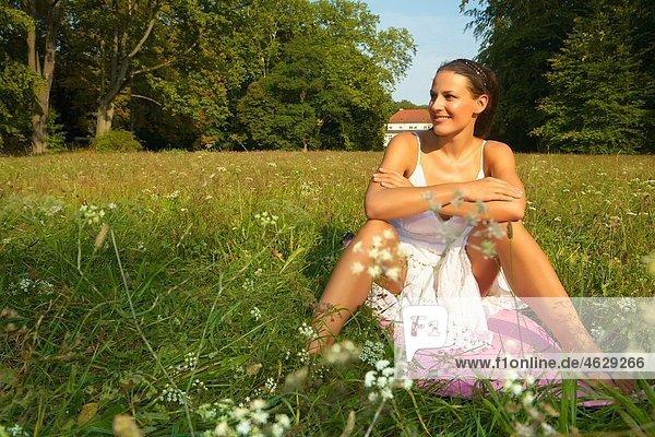 Frau auf einer Wiese sitzend  lächelnd