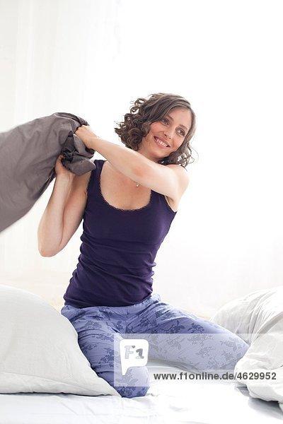 Junge Frau spielt mit Kissen  lächelnd
