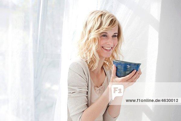 Junge Frau trinkt  lächelt.