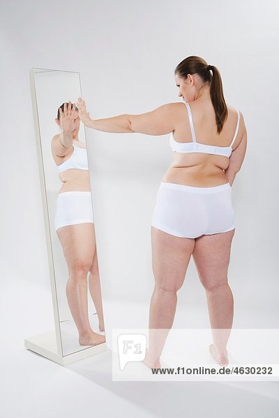 Junge Frau schaut sich selbst in den Spiegel
