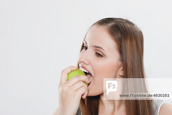 Junge Frau isst grünen Apfel