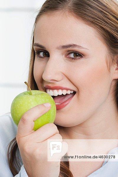Junge Frau mit grünem Apfel  lächelnd  Portrait
