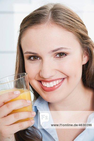 Junge Frau mit einem Glas Saft  lächelnd  Portrait