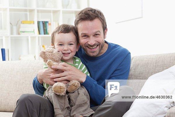 Vater und Junge (2-3 Jahre) auf Sofa  Portrait