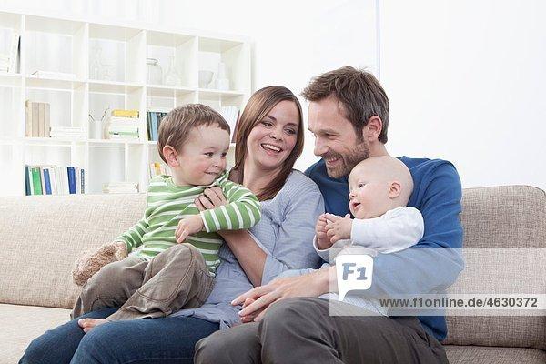 Deutschland  Bayern  München  Familie mit Spaß im Wohnzimmer  Lächeln