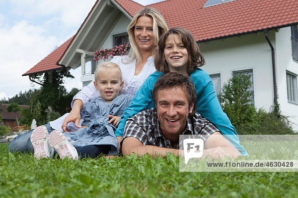 Germany  Munich  Family in front of house  smiling  portrait