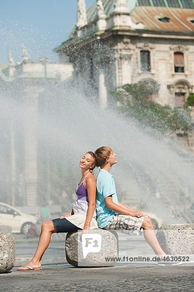 Young man and woman sitting on rock at fountain